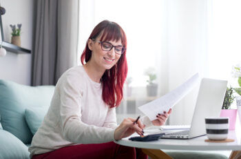 happy-woman-at-home-using-laptop-and-checking-bill-WKHT75B